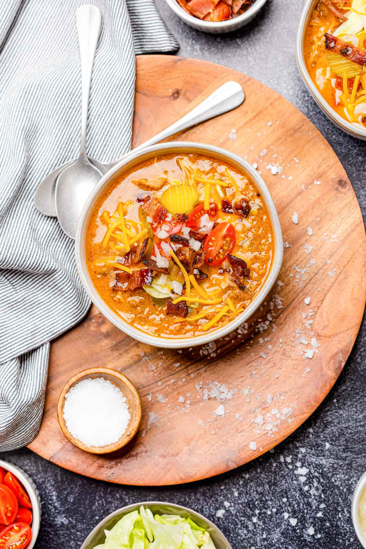 keto cheeseburger soup in a white bowl on a dark backgrounds with a bowl of toppings and a spoon