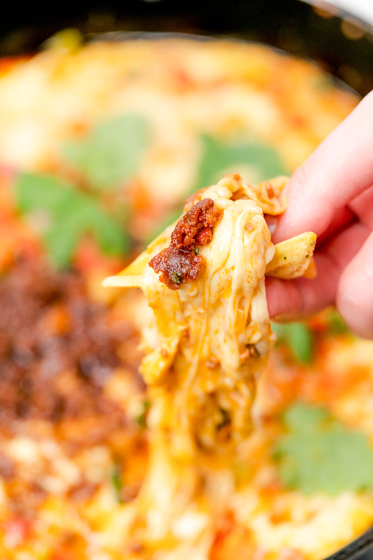 queso fundido with chorizo being scooped up with a tortilla chip