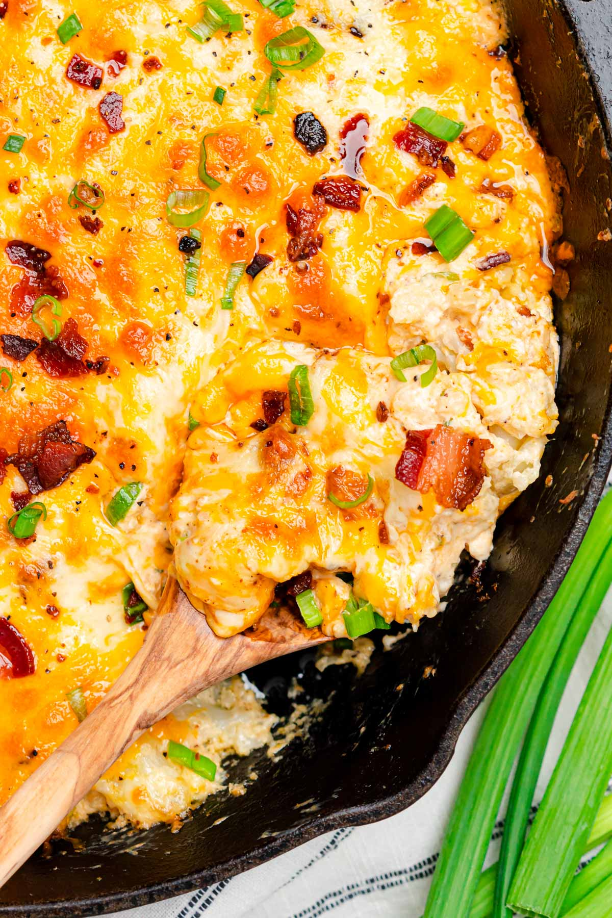 Keto Cauliflower Casserole closeup with a spoon scooping into the casserole to remove a serving.